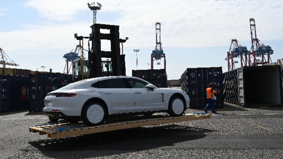 Mitarbeiter der Hafenlogistik in Bremerhaven verladen Porsche Fahrzeuge in Containern, die mit dem Zug über die neue Seidenstrasse nach China gebracht werden.