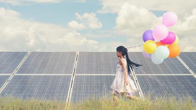 Kind läuft mit Luftballons vor einer Photovoltaikanlage.