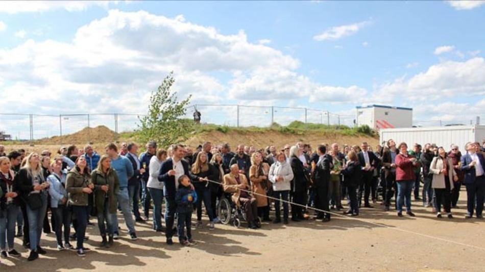 Rund 200 Festgäste blicken gespannt nach oben und lauschen dem Richtspruch des Zimmermanns.