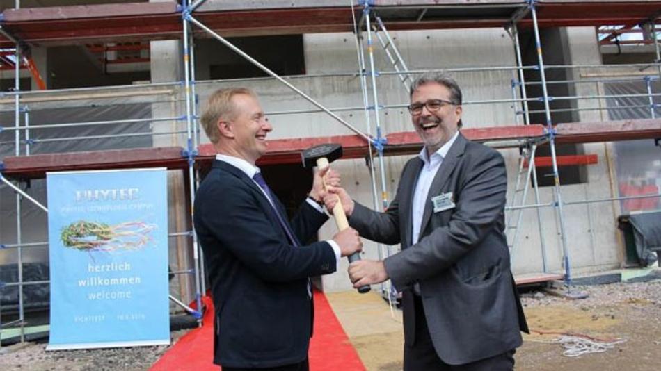 Geschäftsführer Bodo Huber (rechts) überreicht seinem Kollegen Michael Mitezki symbolisch den Hammer für den Bauherrn.