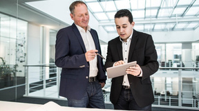 Zwei Männer im Gespräch, in der Hand ein Tablet, auf dem etwas gezeigt wird.