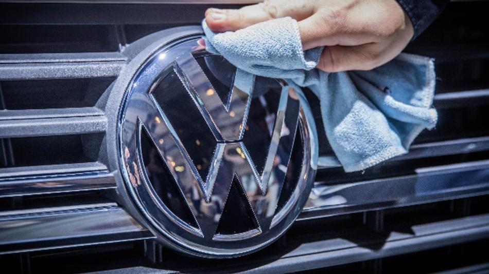 Ein Mitarbeiter poliert das VW-Logo eines VW Passat am Kühlergrill.