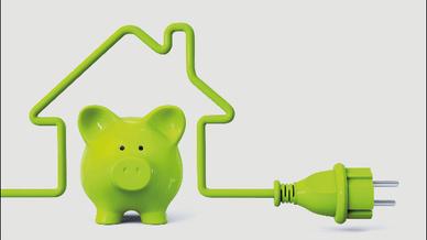 Ein grünes Sparschwein steht in den Umrissen eines Hauses, die von einem grünen Kabel gezeichnet werden