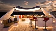 Ausßenszenerie auf einem Schiff mit Bar und Sitzbereichen, beleuchtet von warmem Licht