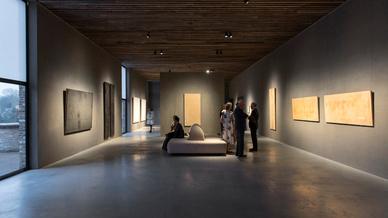 Blick in einen Ausstellungsraum der Gallerie, zwei Personen sitzend links, vier Personen stehend rechts