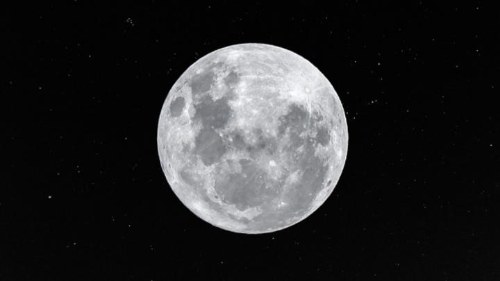 Der Mond mit Sternen im Hintergrund.