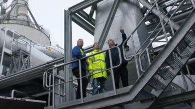 Drei Männer auf einer Metalltreppe außerhalb einer Industrieanlage