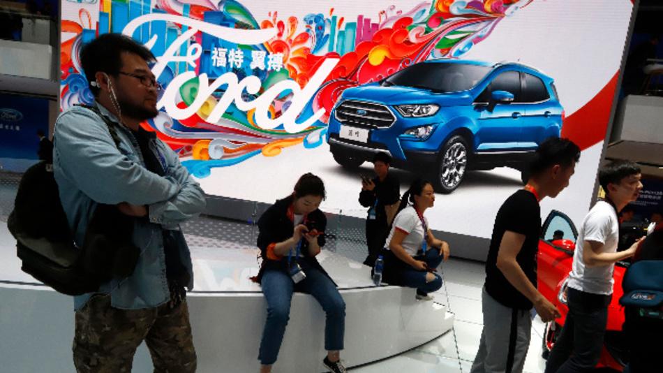 Messebesucher betrachten den Stand von Ford bei der Automesse in Peking.