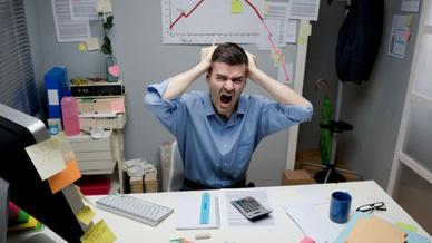 Mann dreht durch vor Schreibtisch