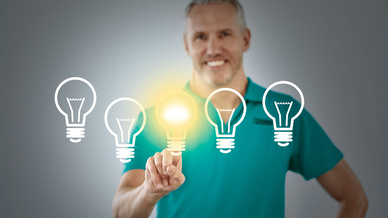 Mann in blauen Polo tippt Grafik von Glühbirne an