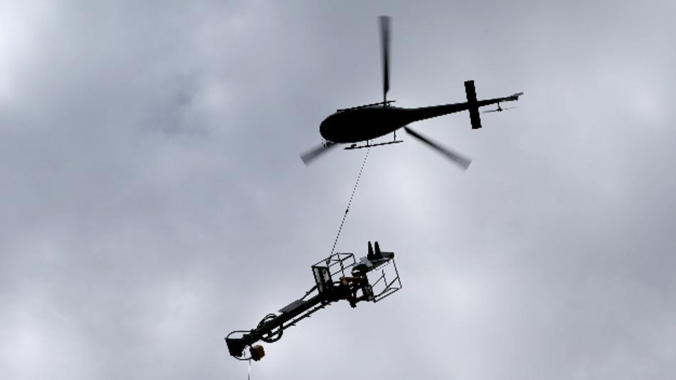 Ein Hubschrauber transportiert über der am Pfingstwochenende 2019 gesperrten Bahnstrecke Augsburg-Donauwörth einen Signalmasten der Bahn.