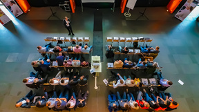 Blick von oben auf Publikum, das einem Vortrag lauscht