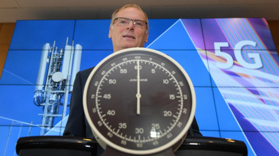 Jochen Homann, Präsident der Bundesnetzagentur, steht vor dem Start der Auktion von 5G-Mobilfunkfrequenzblöcken am Mainzer Technik-Standort der Bundesnetzagentur hinter einer Stoppuhr.