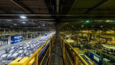 Fabrikhalle, links hell mit LEDs beleuchtet, recht düster mit alten Lampen