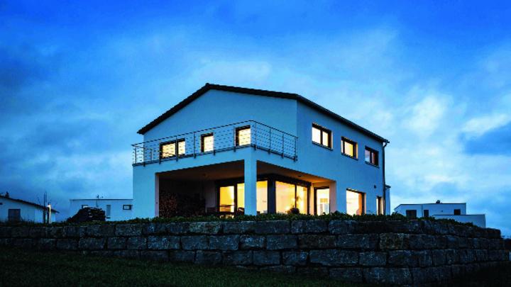Haus in Blautönen von Außen in der Dämmerung, erleuchtete Fenster bilden einen gelben Kontrast