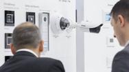 Zwei Männer betrachten einen Ausstellungsstand mit Bewegungsmeldern und Kameras