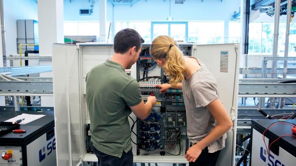 Stefan Oberleitner, Wissenschaftliche Hilfskraft und Franziska Wilfinger, Werkstudentin überprüfen anliegende Spannung an einem experimentellen Gebäudeverteiler im neuen Forschungszentrum.