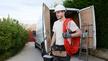 Junger Mann mit Werkzeugkoffer in der Hand und Aufgerolltem Kabel über der Schulter