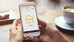 Frauenhände halten Smartphone, auf dem die Benutzeroberfläche der Yale Home App zu sehen ist
