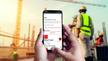 Smartphone wird von zwei Händen gehalten, auf dem Display ist die APP zu sehen, im Hintergrund Bauarbeiter mit Sicherheitswesten auf einer Baustelle.