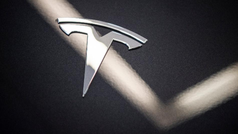 Auf der Motorhaube des Elektroautos Model 3 von Tesla in einem Ausstellungsraum ist das Logo zu sehen.