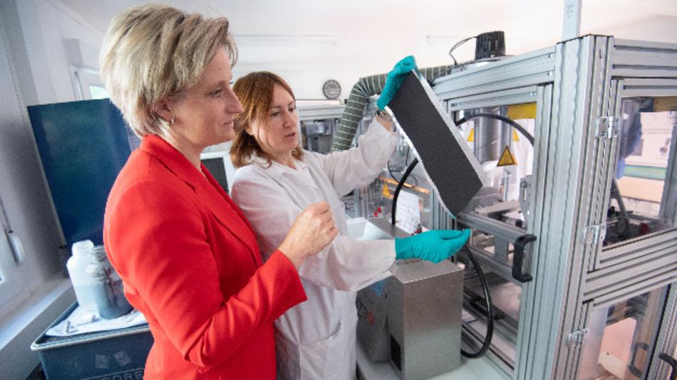 Nicole Hoffmeister-Kraut (CDU, l), Wirtschaftsministerin von Baden-Württemberg, betrachtet mit einer Mitarbeiterin des Fraunhofer-Instituts für Arbeitswirtschaft und Organisation vor einer Beschichtungsmaschine eine beschichtete Elektrode für eine Batteriezelle.