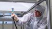 Forscherin prüft Leuchte im Reinraum