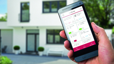 Hand hält Mobiltelefon mit Youvi-App, im Hintergrund ein weißes Haus