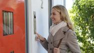 Junge Frau klingelt an Haustür und kommuniziert über Türsprechanlage