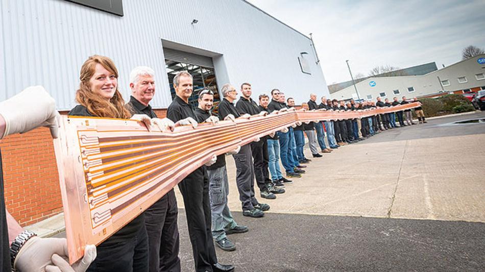 Bild 3. Die Mitarbeiter von Trackwise halten eine 26 m lange, mehrlagige, flexible Leiterplatte. Sie verteilt als Kabelbaum Energie und Signale über die Tragflächen eines unbemannten Flugzeugs.