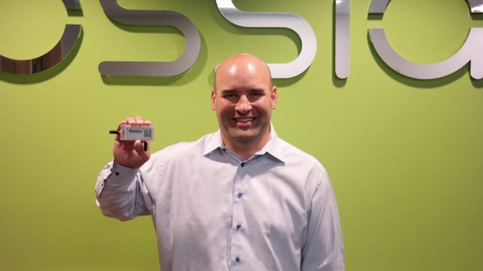 Der Hardware-Chefingenieur von Ossia, Jamie Wojcik, hält das elektronische Regaletikett, das durch kabelloses Energy Harvesting gespeist wird.
