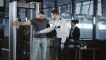 An einem Sicherheitsbereich am Flughafen wird ein Mann mit einem Metalldetektor überprüft.