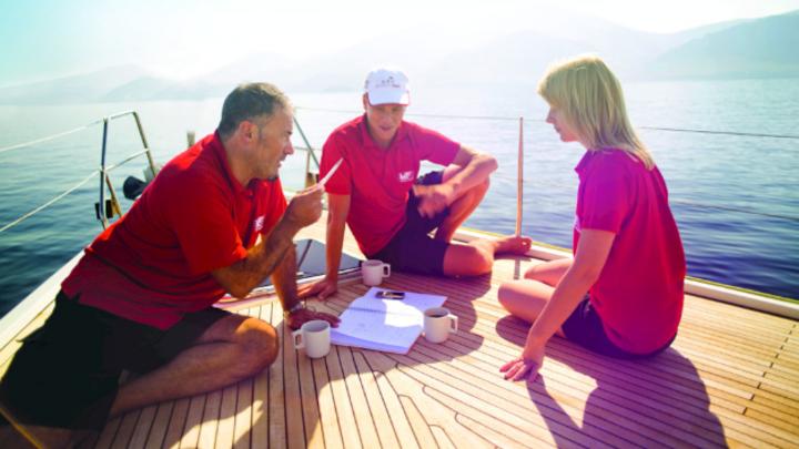 Drei Leute, Tutor und zwei Auszubildende, sitzen auf einem Boot und besprechen etwas in entspannter Atmosphäre.