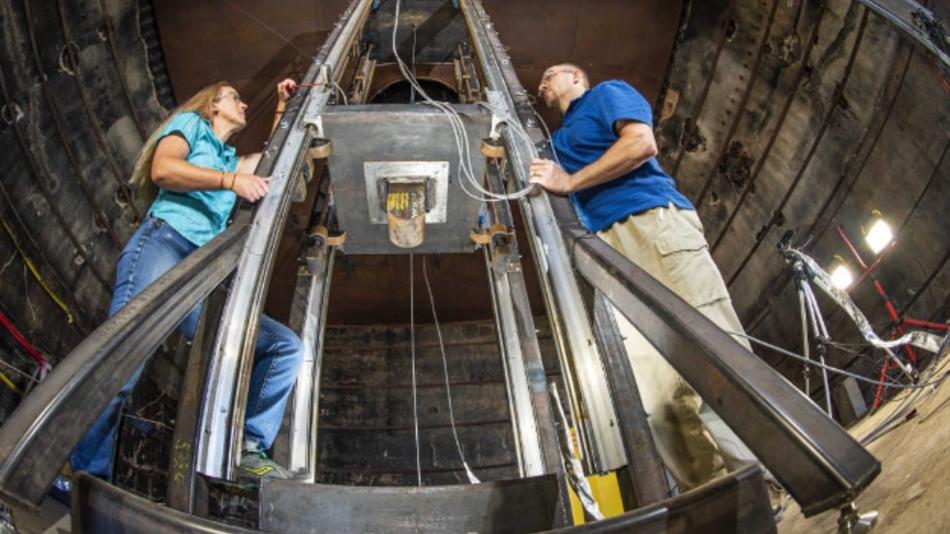 June Stanley (links) und Chris Grosso (rechts) neben ihrem Fallturm in den Sandia National Laboratories, mit dem sie Lithium-Ionen-Zellen testen.