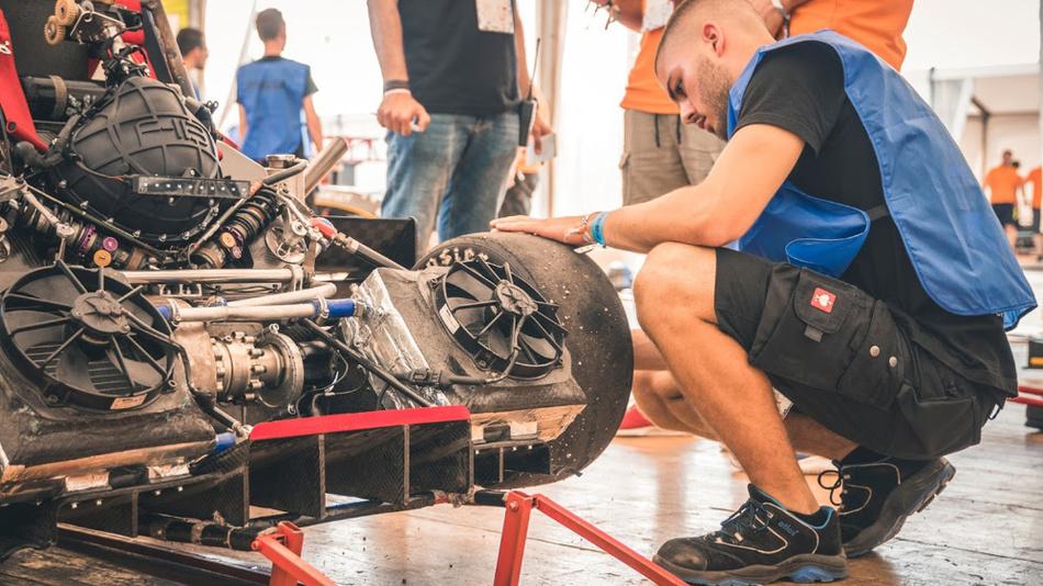 Ein Teammitglied trifft Vorbereitungen am Rennwagen, damit alle technischen Prüfungen absolviert werden können.