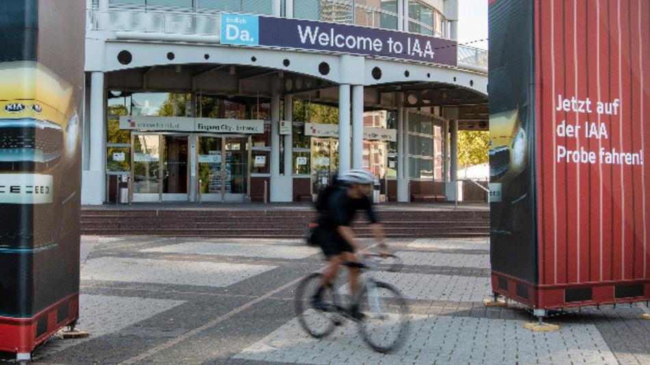 Ein Fahrradfahrer fährt vor dem Schriftzug »Welcome to IAA« vorbei. Die Automesse findet vom 12. bis zum 22. September auf dem Messegelände in Frankfurt am Main statt.