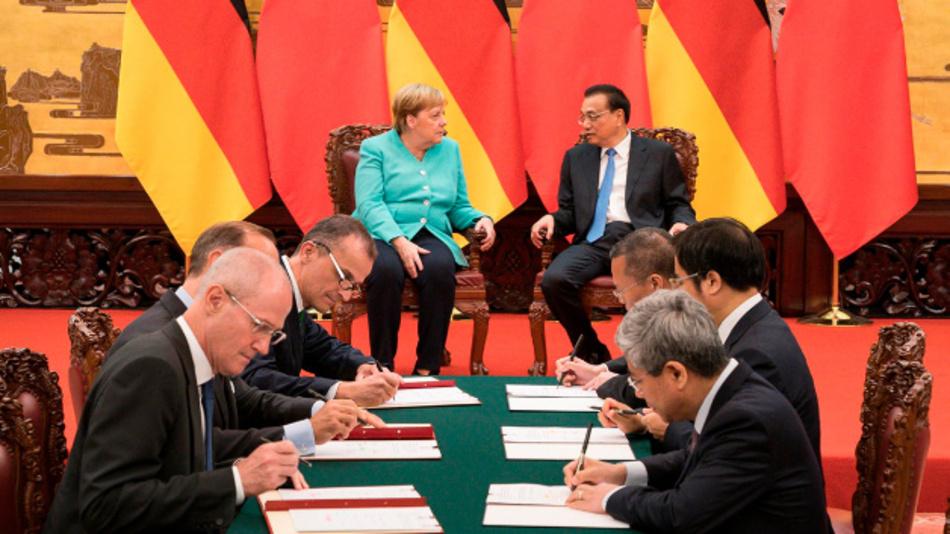 Unterschriftenzeremonie zwischen Schaeffler und der chinesischen Provinz Hunan zur Förderung des autonomen Fahrens – Bundeskanzlerin Dr. Angela Merkel und der chinesische Ministerpräsident Li Keqiang im Hintergrund.