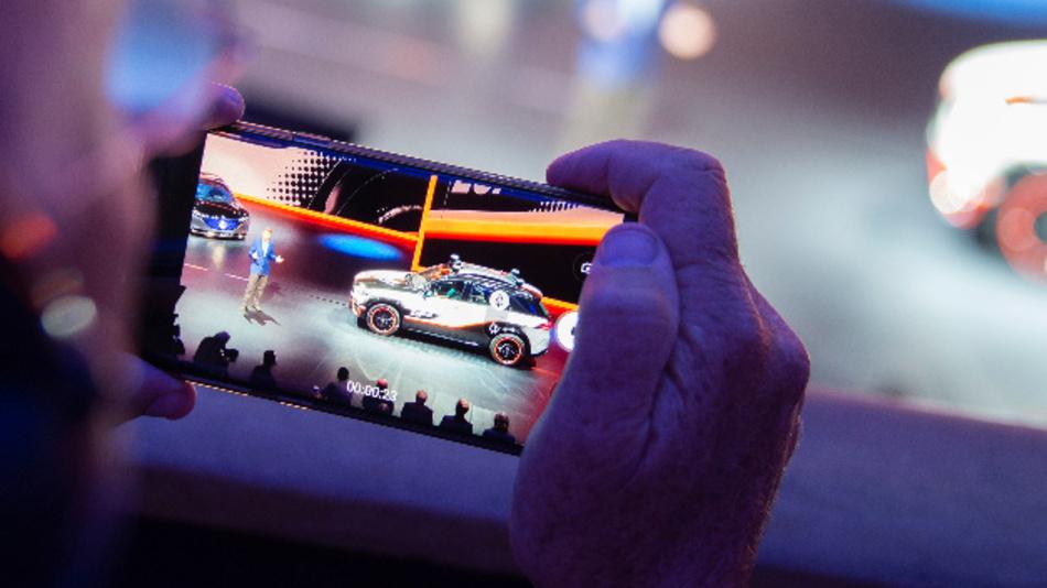 Ein Zuschauer filmt mit seinem Handy die Präsentation von Mercedes auf der IAA.