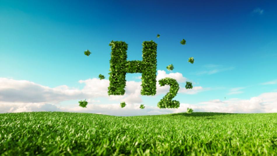 Grüner Schriftzug »H2« oberhalb einer grünen Wiese vor einem blau-weißen Himmel.