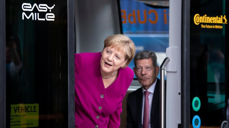 Bundeskanzlerin Angela Merkel (CDU) schaut bei ihrem Eröffnungsrundgang auf der IAA neben Bernhard Mattes, Präsident des Verbands der Automobilindustrie (VDA), aus einem Robo-Taxi Cube.