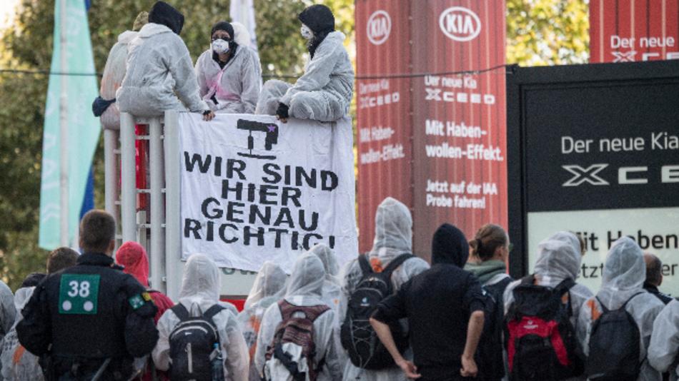 Aktivisten von »Sand im Getriebe« blockieren den Haupteingang der IAA. Dabei sind mehrere Teilnehmer auf ein Schild geklettert und hängen ein Transparent auf »Wir sind hier genau richtig«.