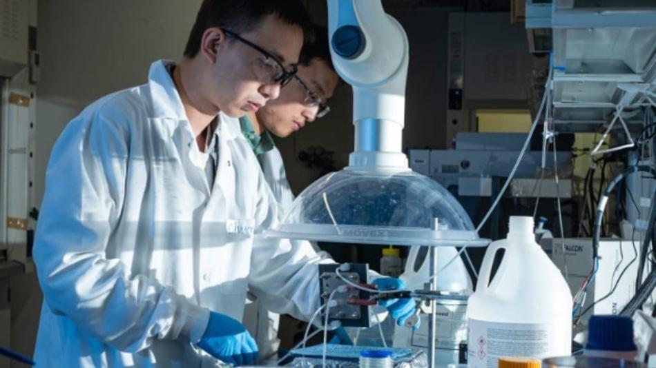Der Postdoktorand Chuan Xia, links, und der Chemie- und Biomolekular-Ingenieur Haotian Wang passen ihren elektrokatalytischen Reaktor an, um aus Kohlendioxid flüssige Ameisensäure herzustellen.