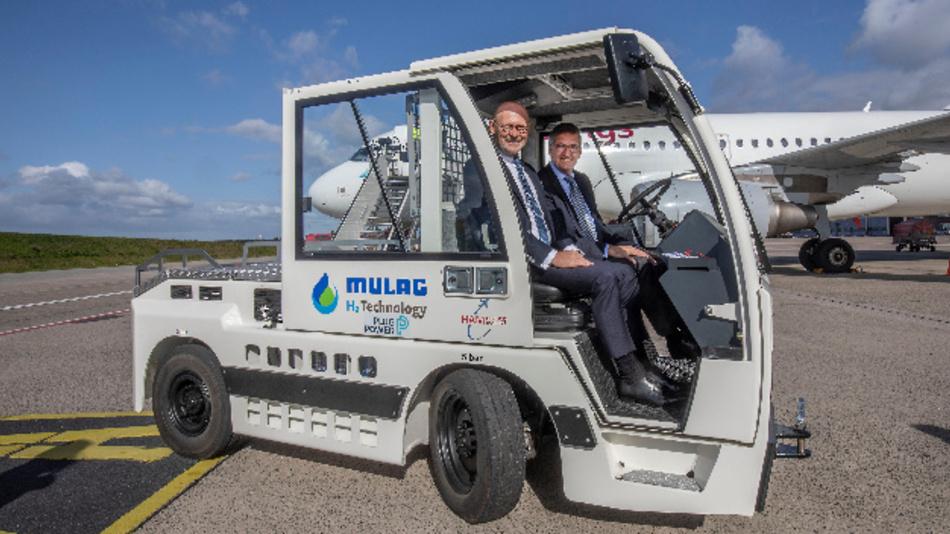 Hamburgs Wirtschaftssenator Michael Westhagemann (l) und Flughafen-Chef Micheal Eggenschwiler (r) im neuen wasserstoffbetriebenen Brennstoffzellen-Schlepper auf dem Vorfeld des Flughafens Hamburg.