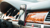 Mobiltelefon vor einem Lüftungsgitter im Fahrzeug