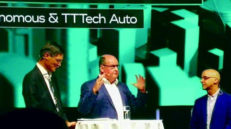 """图 1TTTech Auto 联合创始人 Ricky Hudi(中)和首席执行官 Georg Kopetz(左)向主持人 Robert Siegel 解释为什么发起""""无人驾驶""""首倡活动。"""