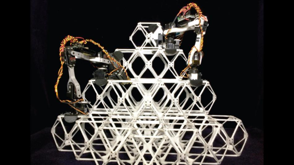 Zwei Roboter bauen eine Struktur aus Voxels auf.