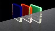 Lumineszierende Gläser leuchten unter ultraviolettem (UV) Licht (oberer Bildteil) und sind unter Raumlicht transparent (unterer Bildteil). Der Farbeindruck wird durch den verwendeten Dotierstoff bestimmt: blau (Thulium), rot (Europium) und grün (Terb