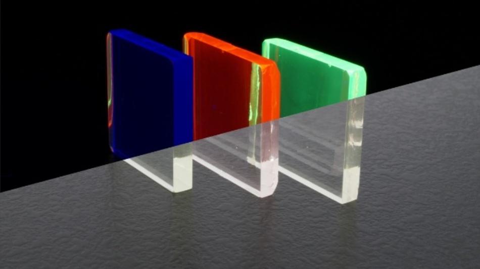 Lumineszierende Gläser leuchten unter ultraviolettem (UV) Licht (oberer Bildteil) und sind unter Raumlicht transparent (unterer Bildteil). Der Farbeindruck wird durch den verwendeten Dotierstoff bestimmt: blau (Thulium), rot (Europium) und grün (Terbium).