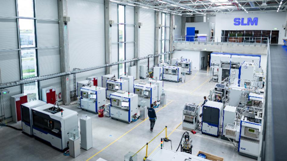 Techniker des Unternehmens SLM Solutions Group arbeiten in der Werkshalle an Metall verarbeitenden 3D-Druckern.