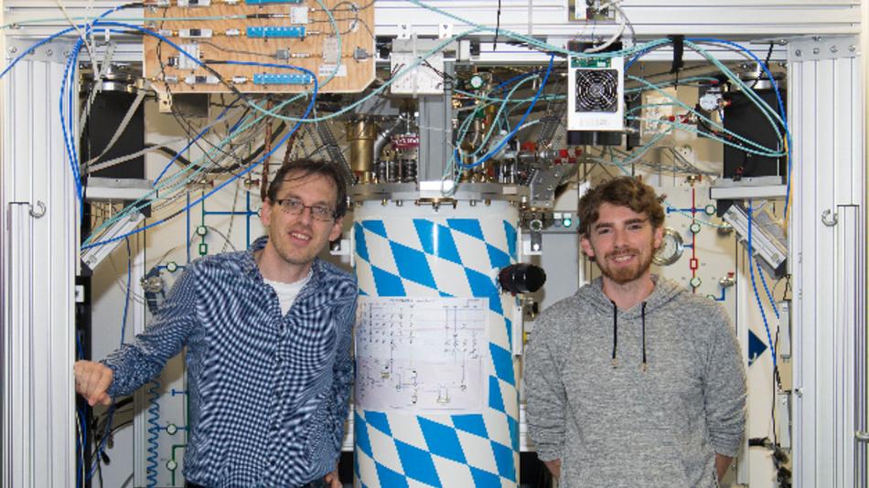 Erstautor Stefan Pogorzalek (r) und Mitautor Dr. Frank Deppe mit dem Kryostaten, in dem sie das Quanten-LAN erstmalig realisiert haben.